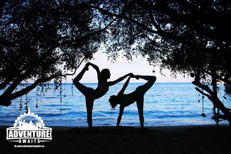 Silhouette of Julia Cobban and friend doing yoga on the beach