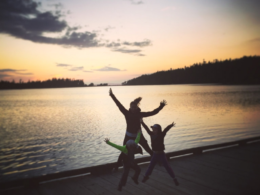 family-jumping-on-dock-during-sunset