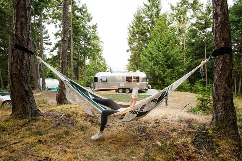 This relaxing photo features Woods on Pender Airstream in the background with a reader relaxing in a hammock. Photo credit belongs to Woods on Pender.