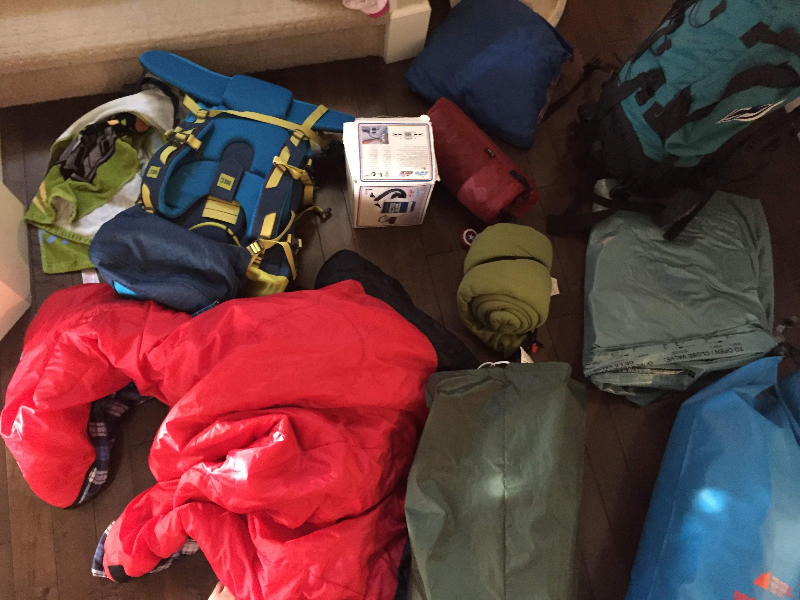 pile of camping gear by the door for how to pack for a last minute camping trip
