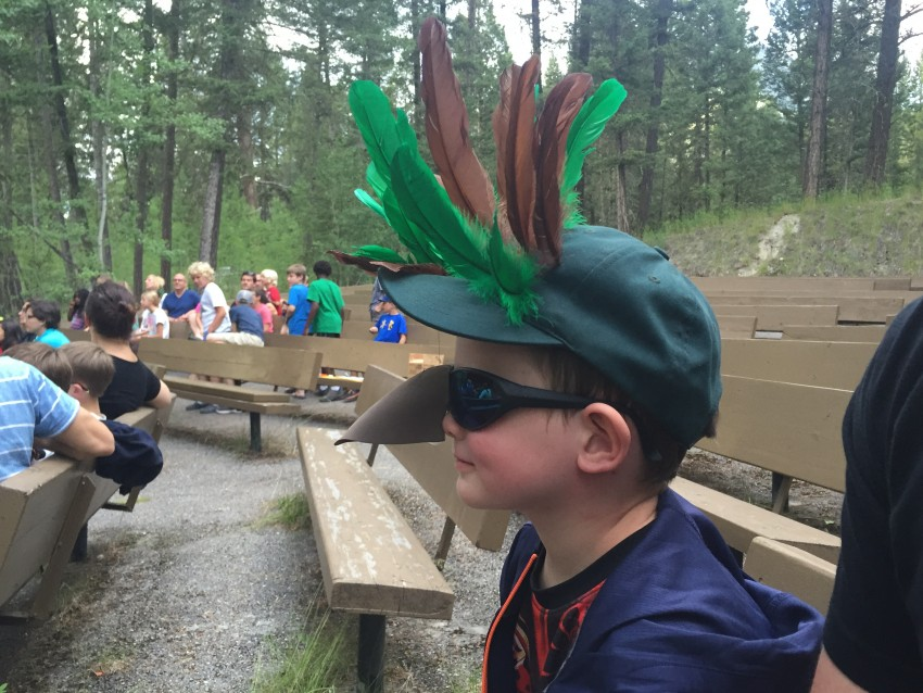 Boy wearing feathers in his hat and a bird beak on his nose