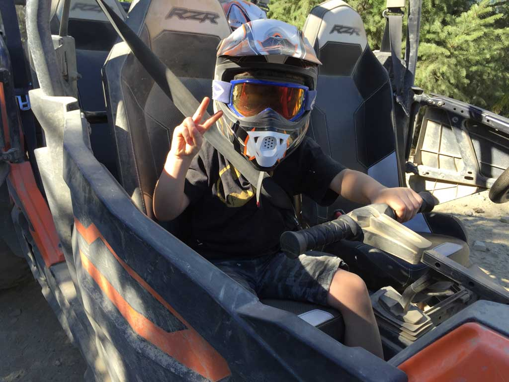 boy sitting in front seat of RZR during Whistler ATV Tours