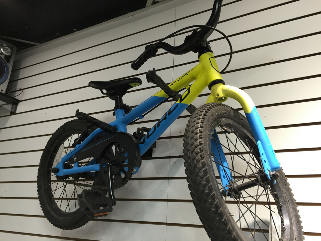 kids mountain bike hanging on the wall in store