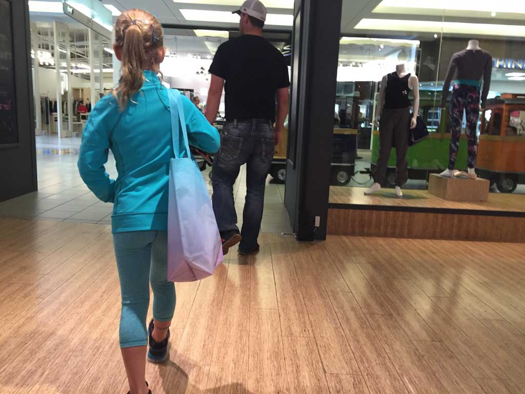 girl leaving Ivivva Metrotown store with shopping bag