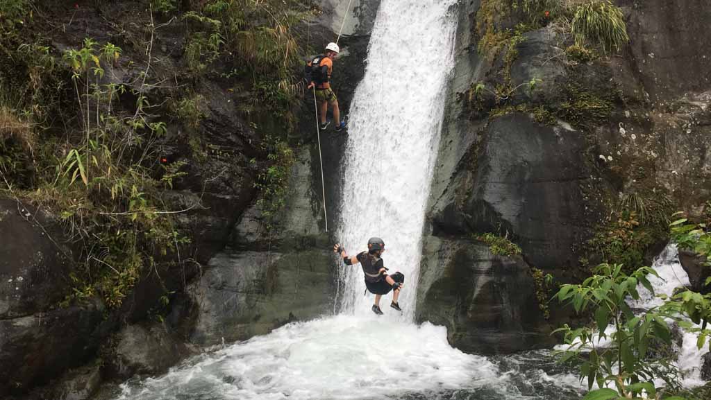 woman jumping into waterfall after reppelling down