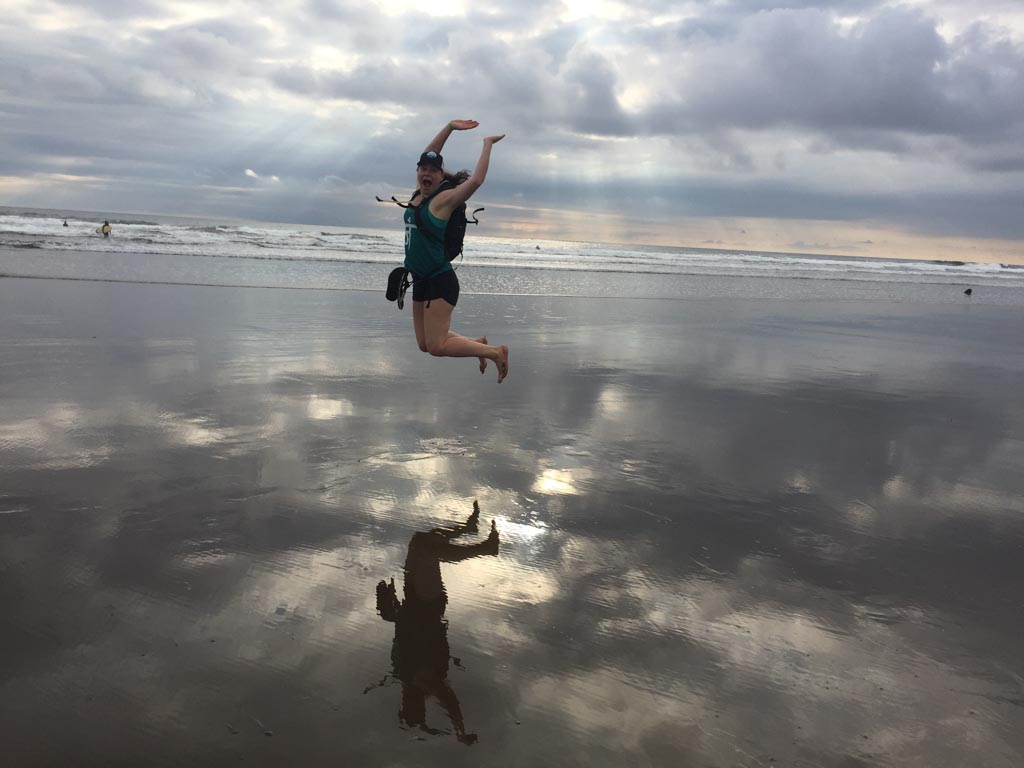 woman jumping on beach in costa rica