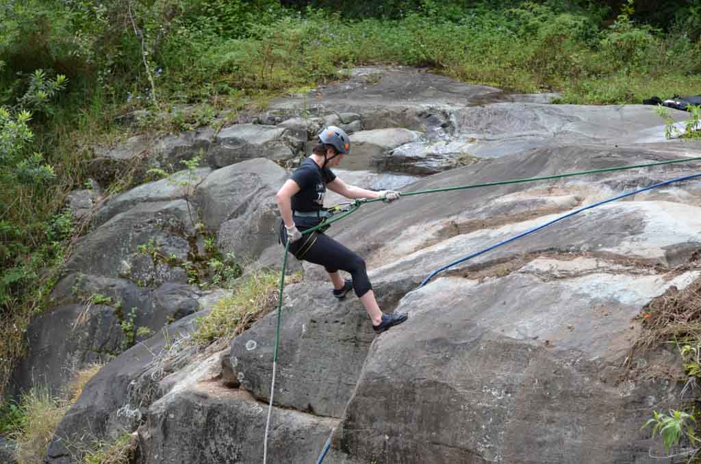 woman reppelling down a rock face in costa rica