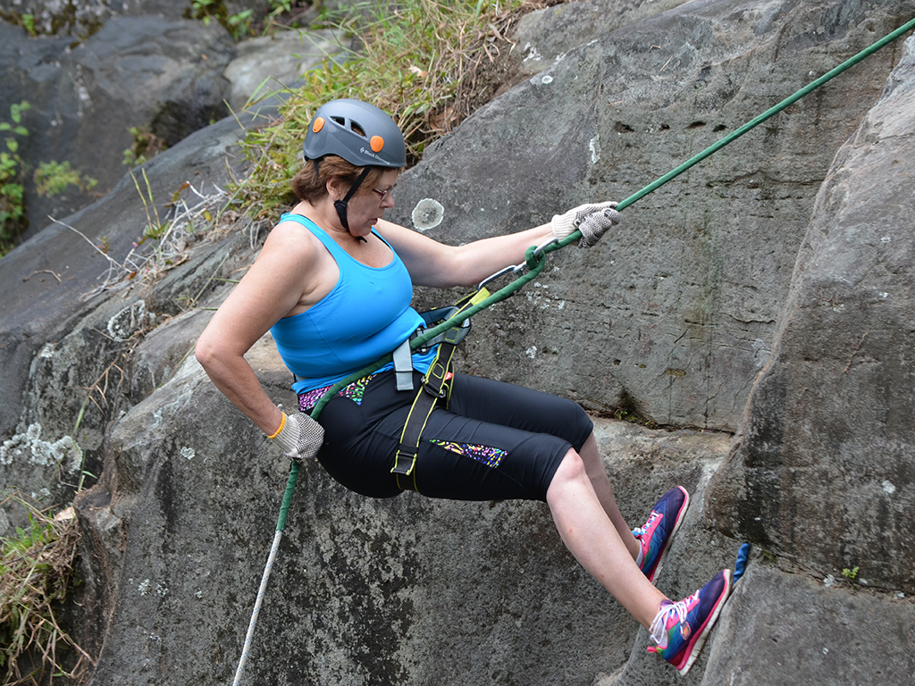 woman reppelling down a steep rock cliff in costa rica