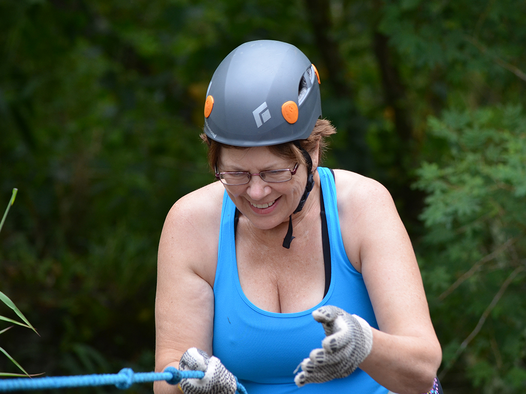 woman smiling because she was able to finish her reppelling down a cliff face