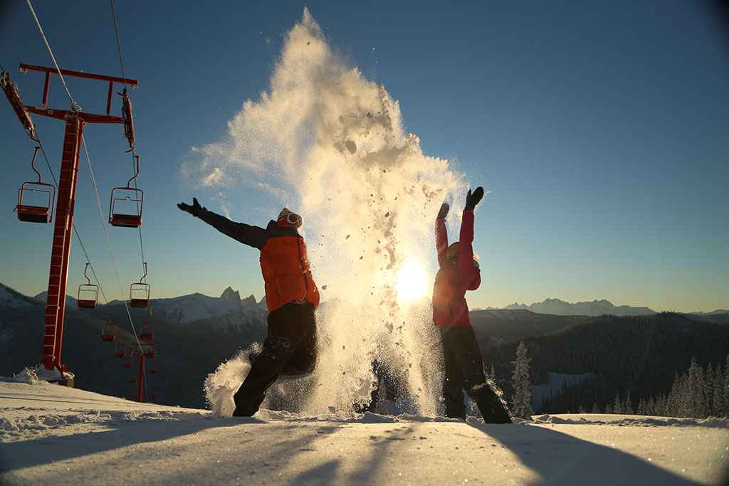 Two people throwing snow in Manning Park, one of the best family ski resorts in BC
