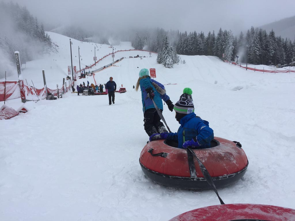 girl pulling boy on tube in Whistler tube park