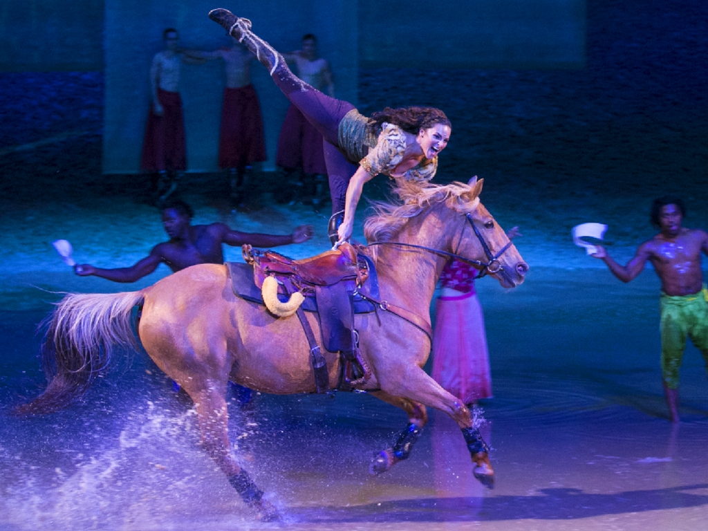 stunt woman rider on horse in Cavalia Odysseo show