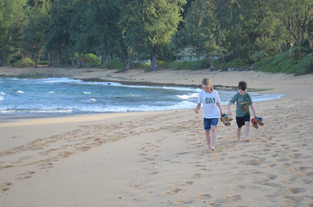 kids walking on the beach in front of the Hanalei Colony Resort