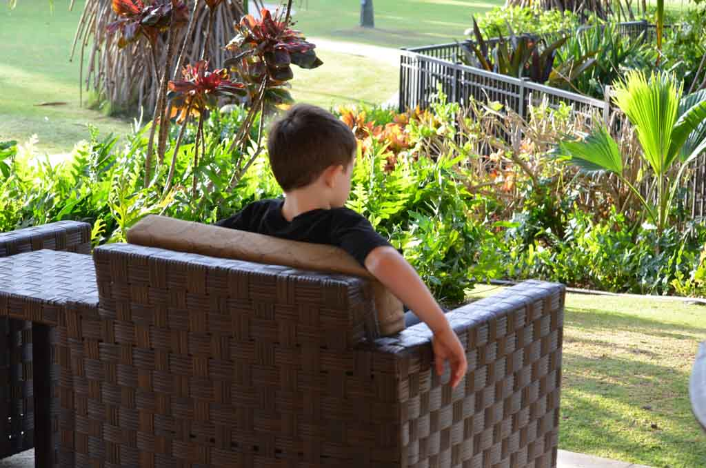 Boy relaxing outside on a patio chair