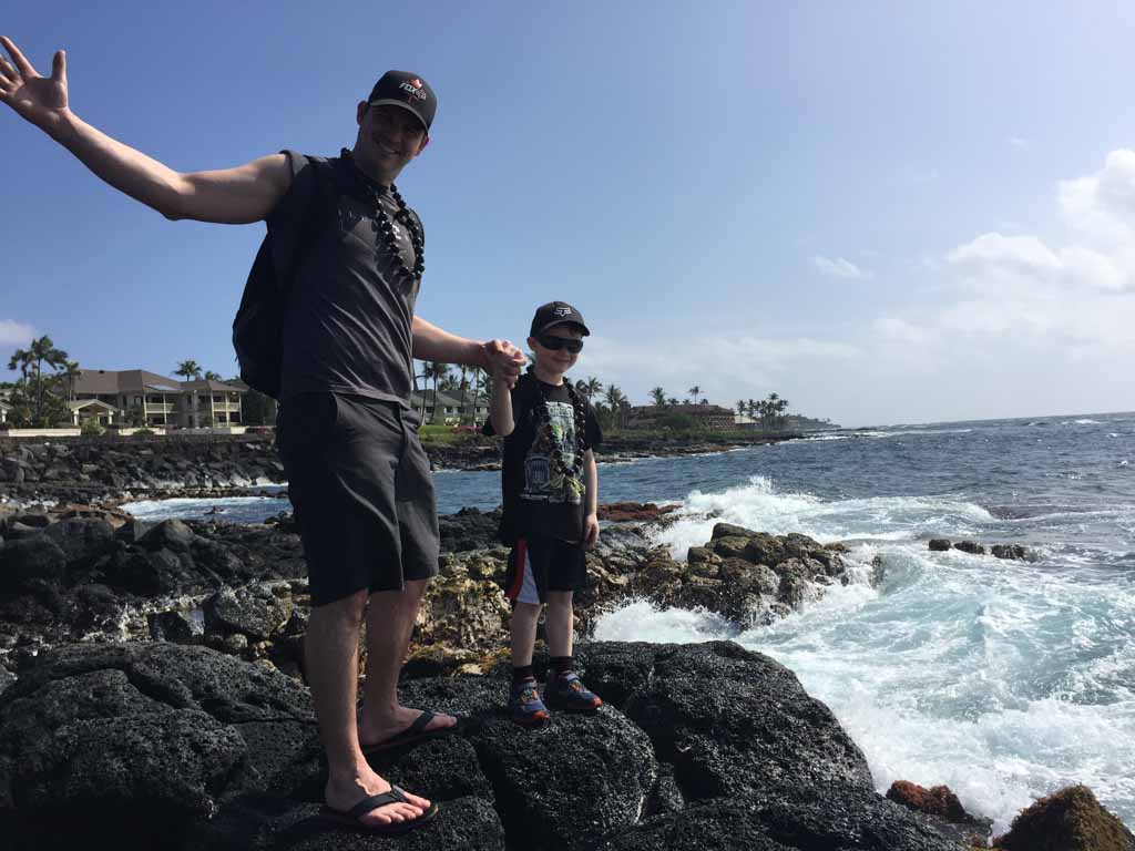 Father and son standing on large rocks by the water