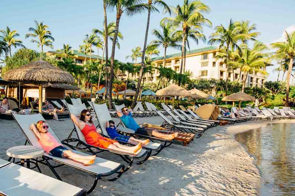 family-relaxing-on-beach-kauai