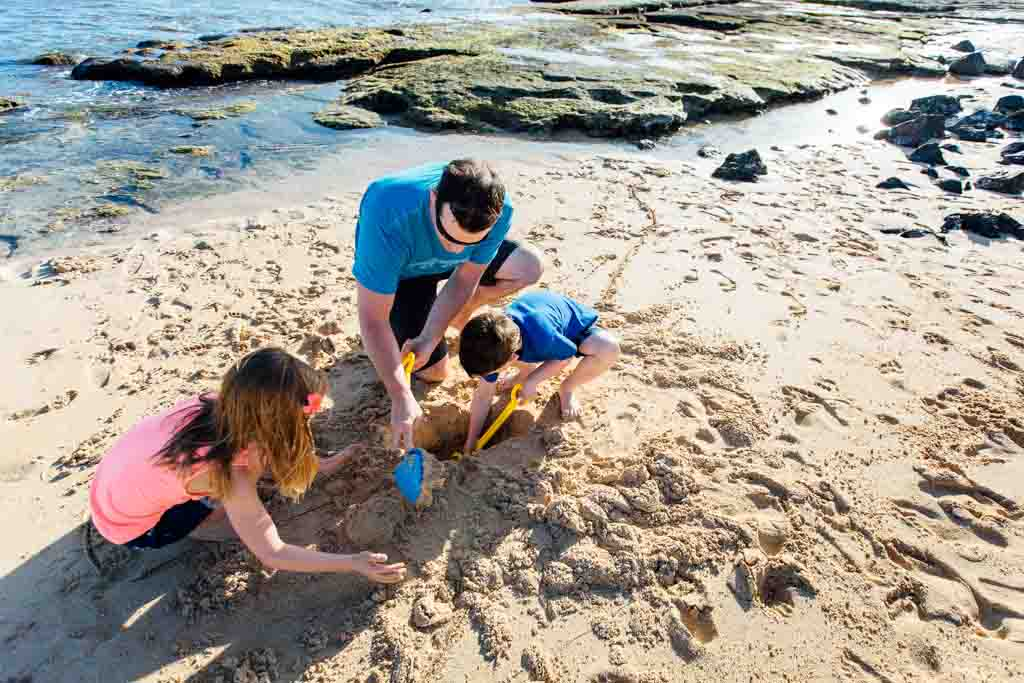 Photo of a family building sandcastles on the beach taken by the best family photographer in Kauai