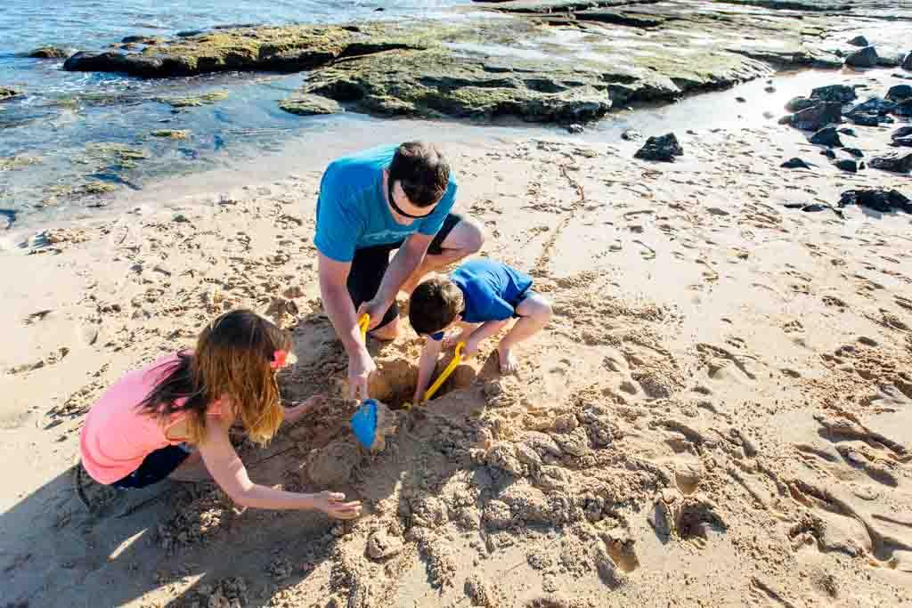 kids-and-dad-building-sandcastles-kauai