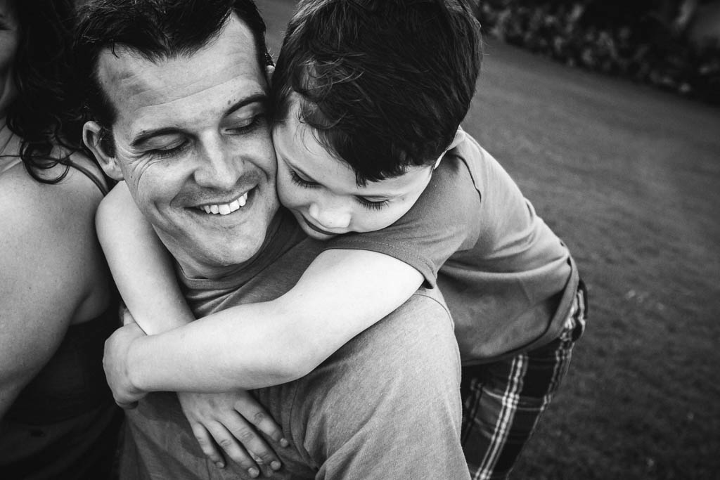 Photo of a boy hugging his dad taken by the best family photographer in Kauai