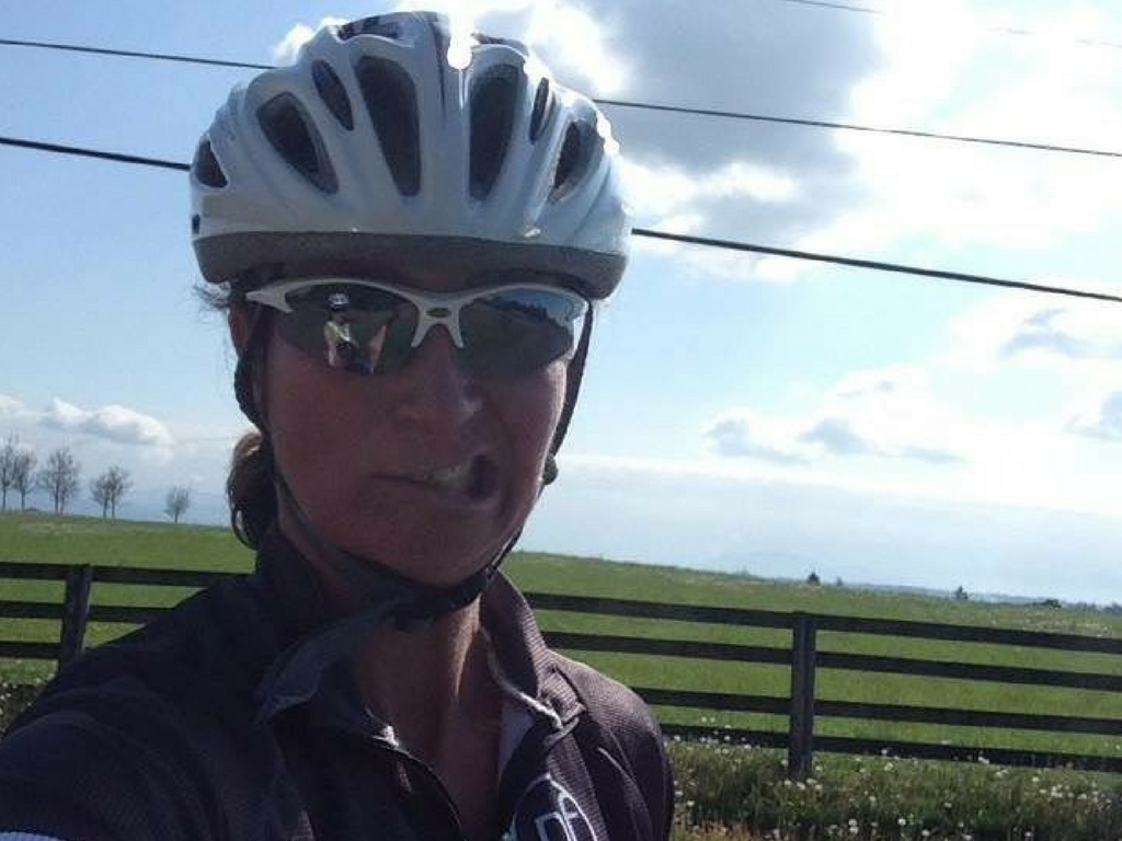 woman-making-funny-face-on-road-bike