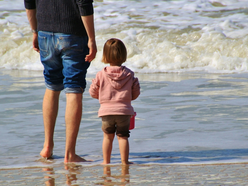 dad-and-daughter-standing-on-beach-looking-at-ocean