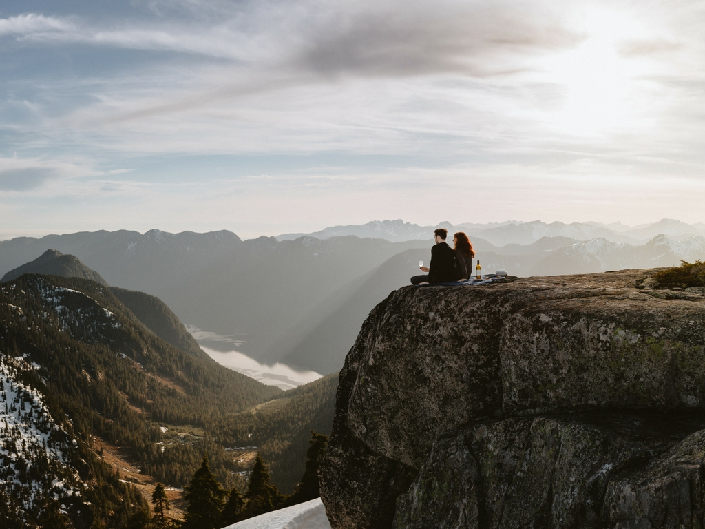 People sitting on a mountain during a helicopter ride break