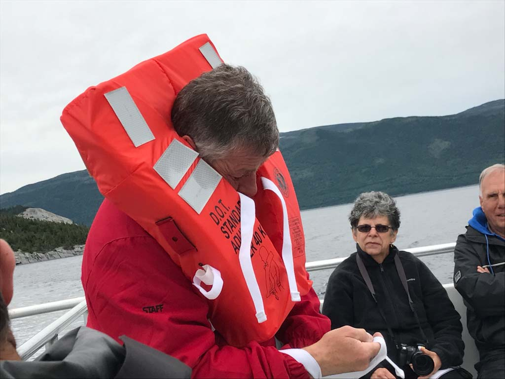 Host showing how to wear a life jacket on our Gros Morne Boat Tours