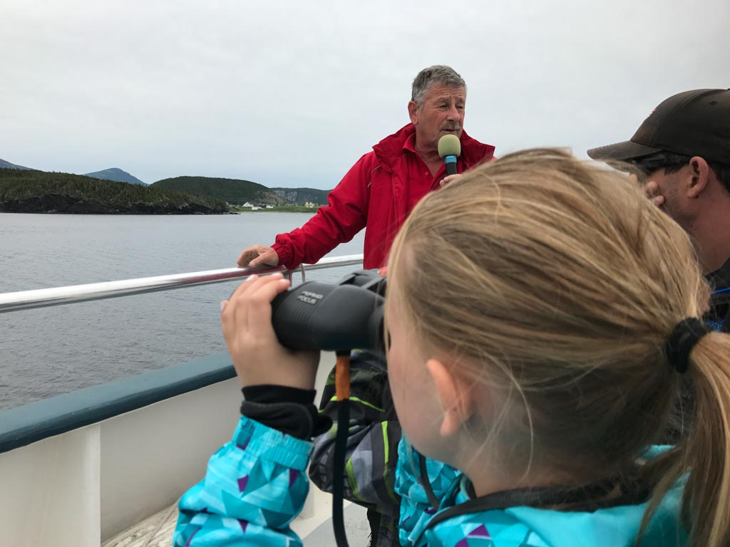 Girl using self focusing binoculars on our Gros Morne boat tours