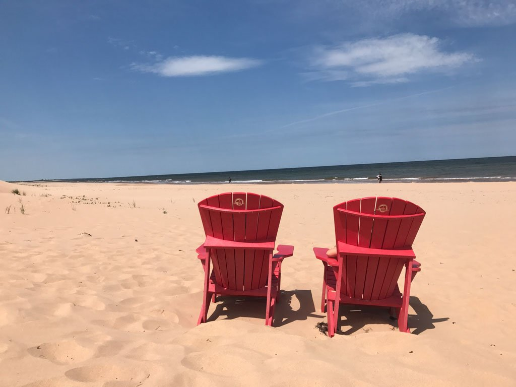 Red lawn chairs on the beach at the PEI National Park