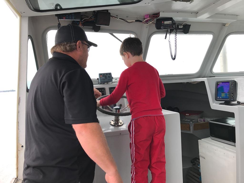 boy-driving-lobster-boat