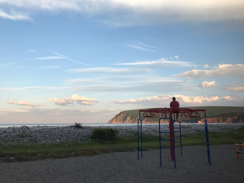 man-on-playground-watching-sunset-over-ingonish-beach