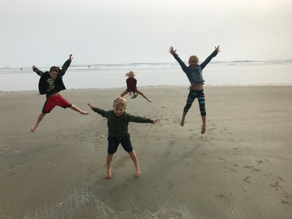 kids-jumping-on-beach-on-vancouver-island