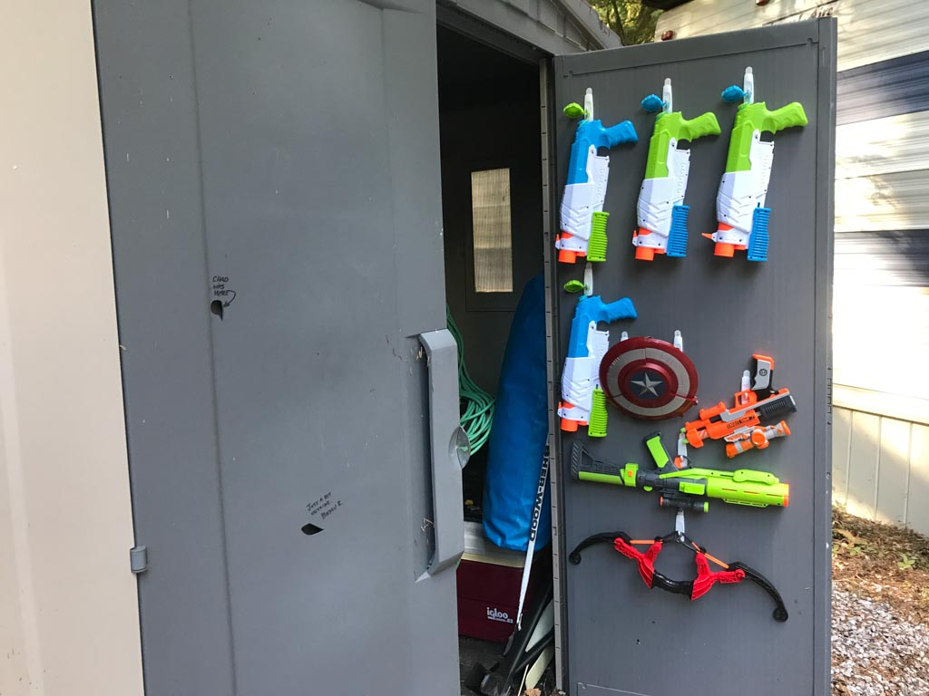 Cabinet of nerf and water guns for the best outdoor gifts for kids