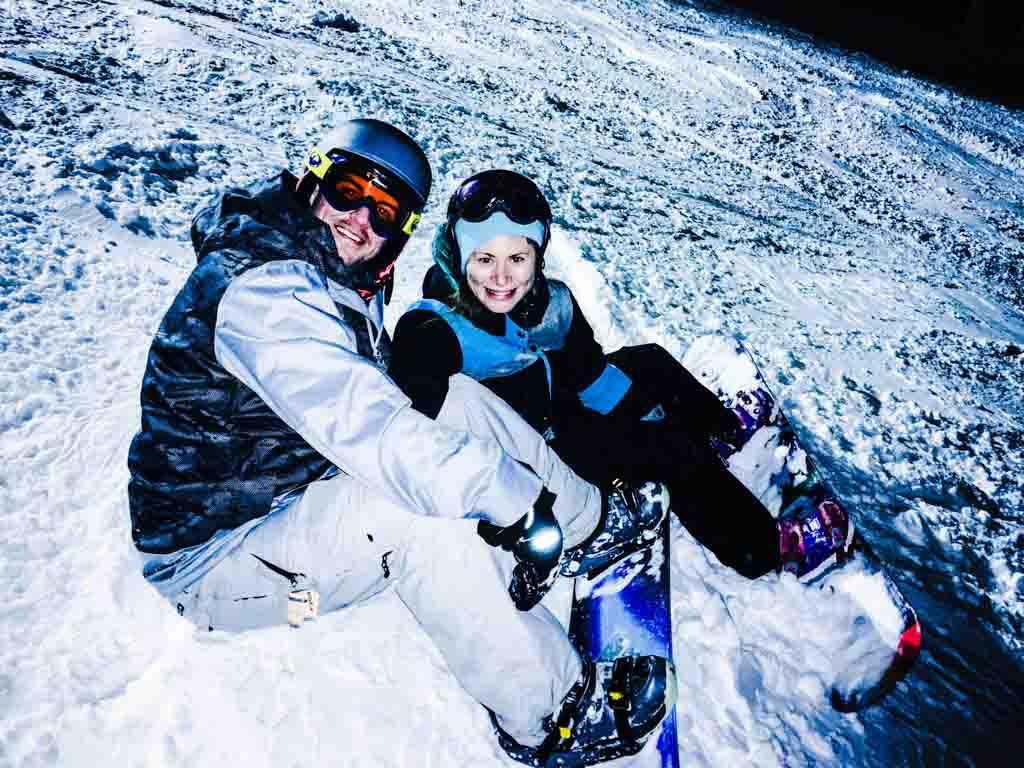 Jami Savage and husband snowboarding on their Big White family ski trip