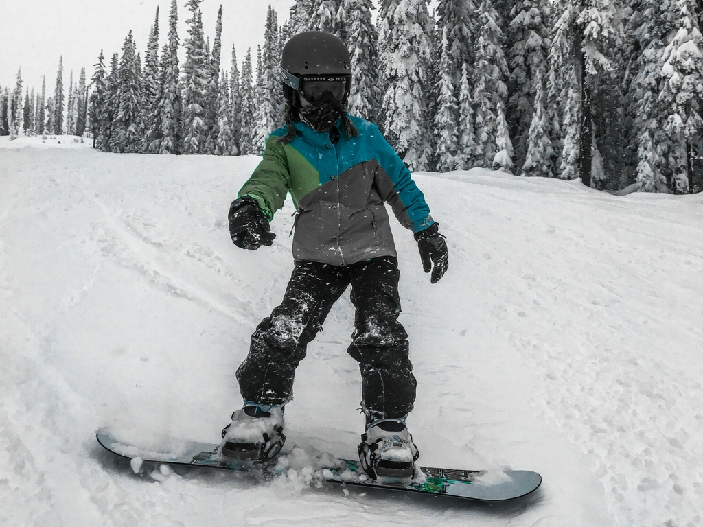 Girl snowboarding on a Big White family ski trip