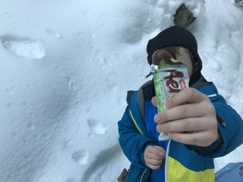 boy-holding-chocolate-bar-on-snowshoe-hike