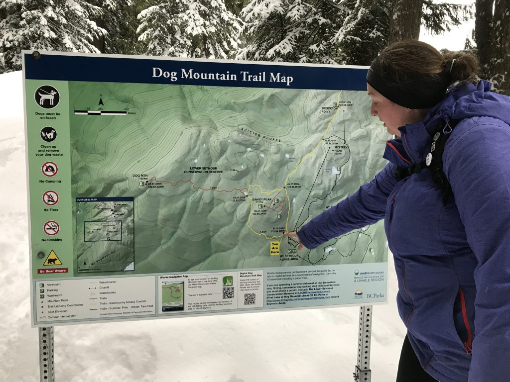 woman-checking-out-dog-mountain-trailhead-sign
