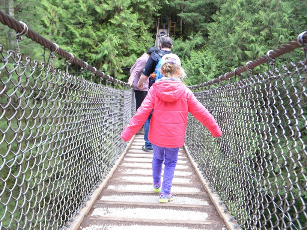 Girl walking over Lynn Canyon suspension bridge for Free Spring Break Activities in Vancouver
