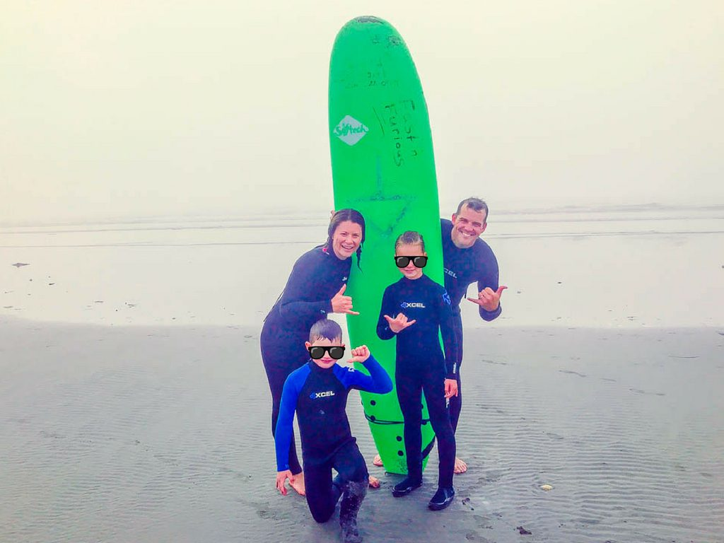 Family posing with surf board on beach for bc road trips activity