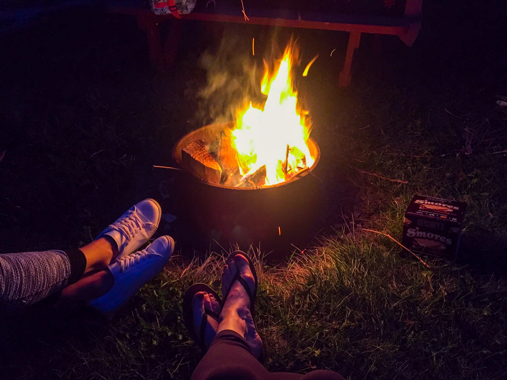 spruce-bay-summer-resort-feet-in-front-of-campfire-at-night