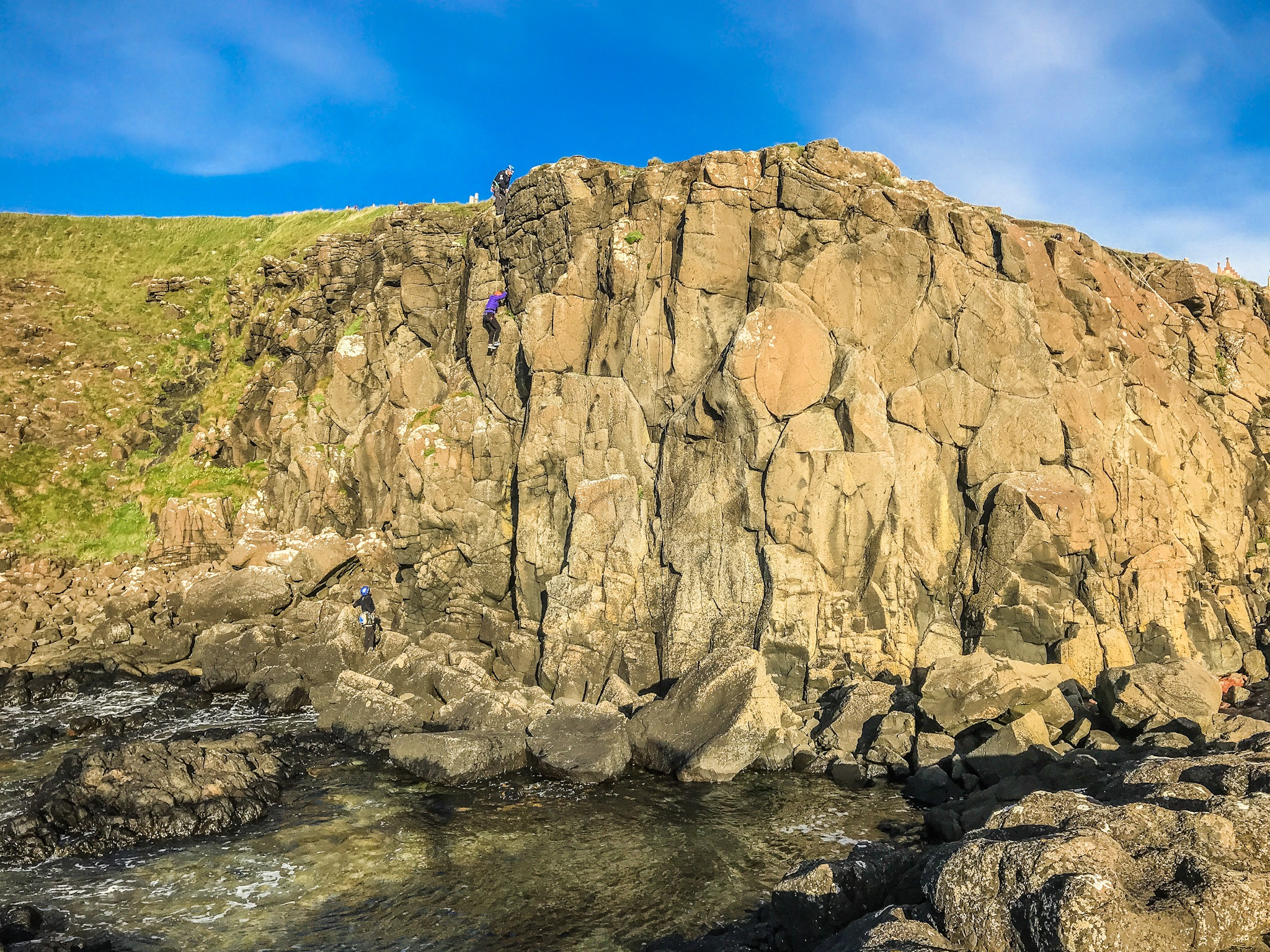 people-climbing-giants-causeway-in-ireland