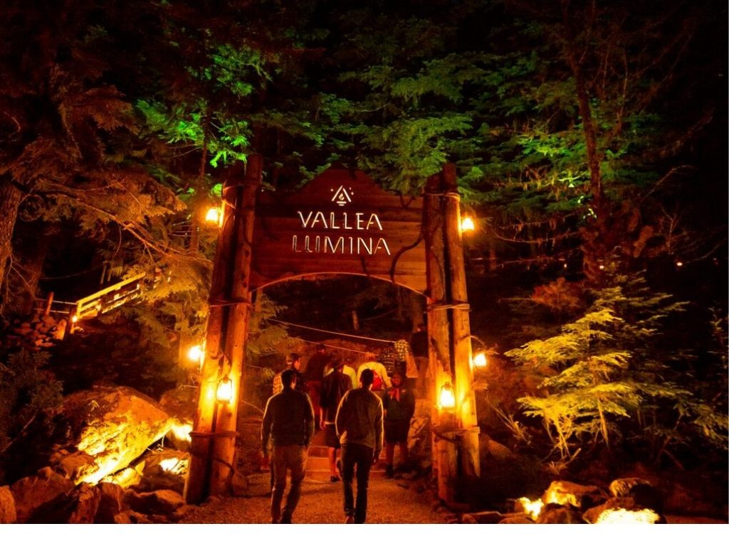 people walking under large vallea lumina review sign