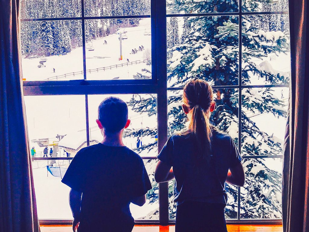 boy-and-girl-looking-out-sun-peak-hotel-window