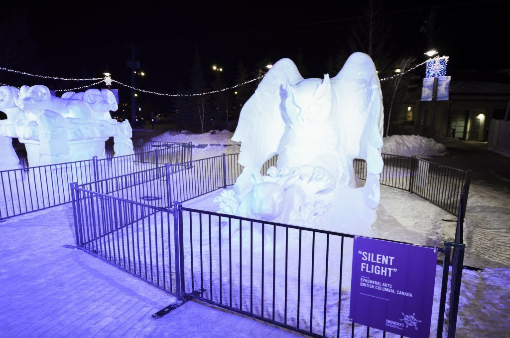 Snow sculpture of owl grabbing a rabbit at Banff SnowDays Festival