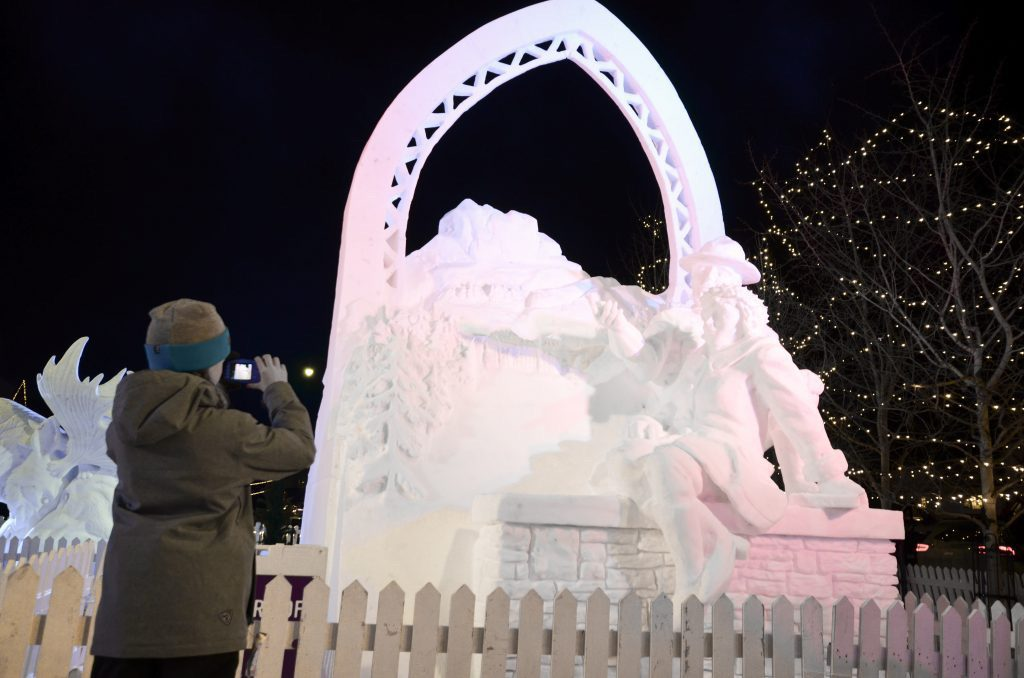 Girl taking a photo of a snow sculpture of scenery at Banff SnowDays Festival