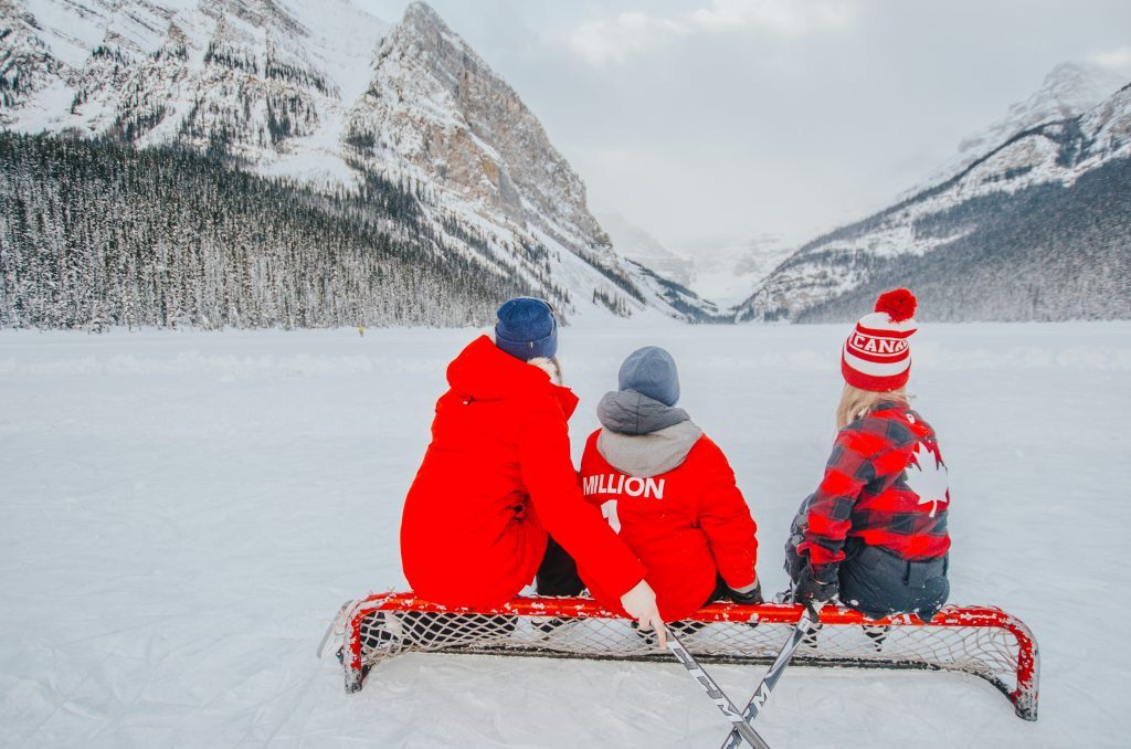family-sitting-on-frozen-lake-louise