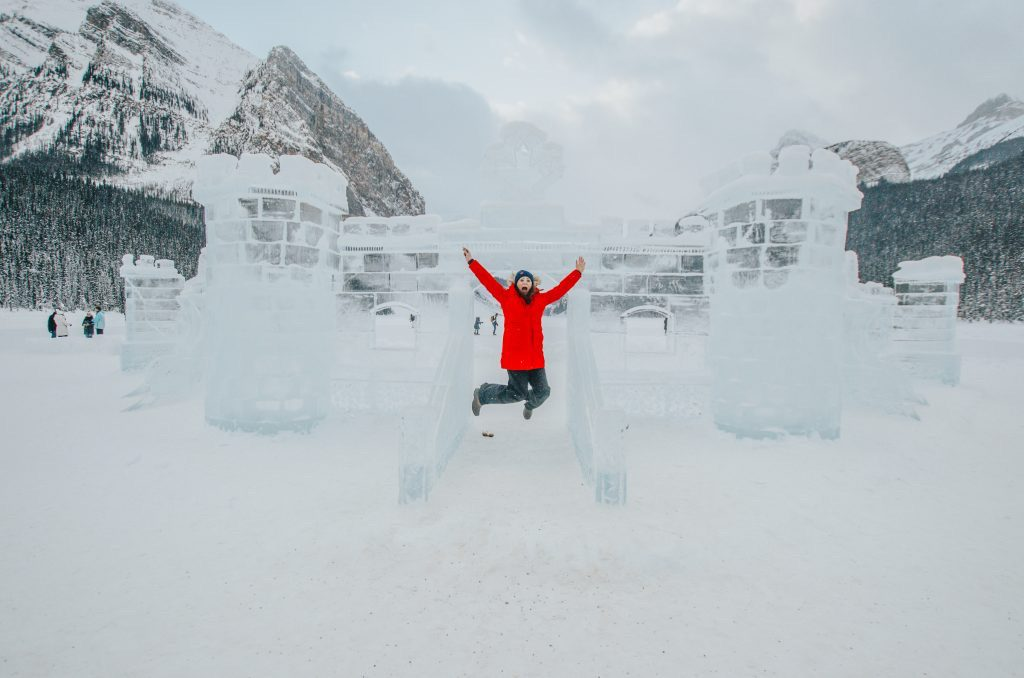 Jami Savage jumping in front of ice castle at the Lake Louise Ice Magic Festival