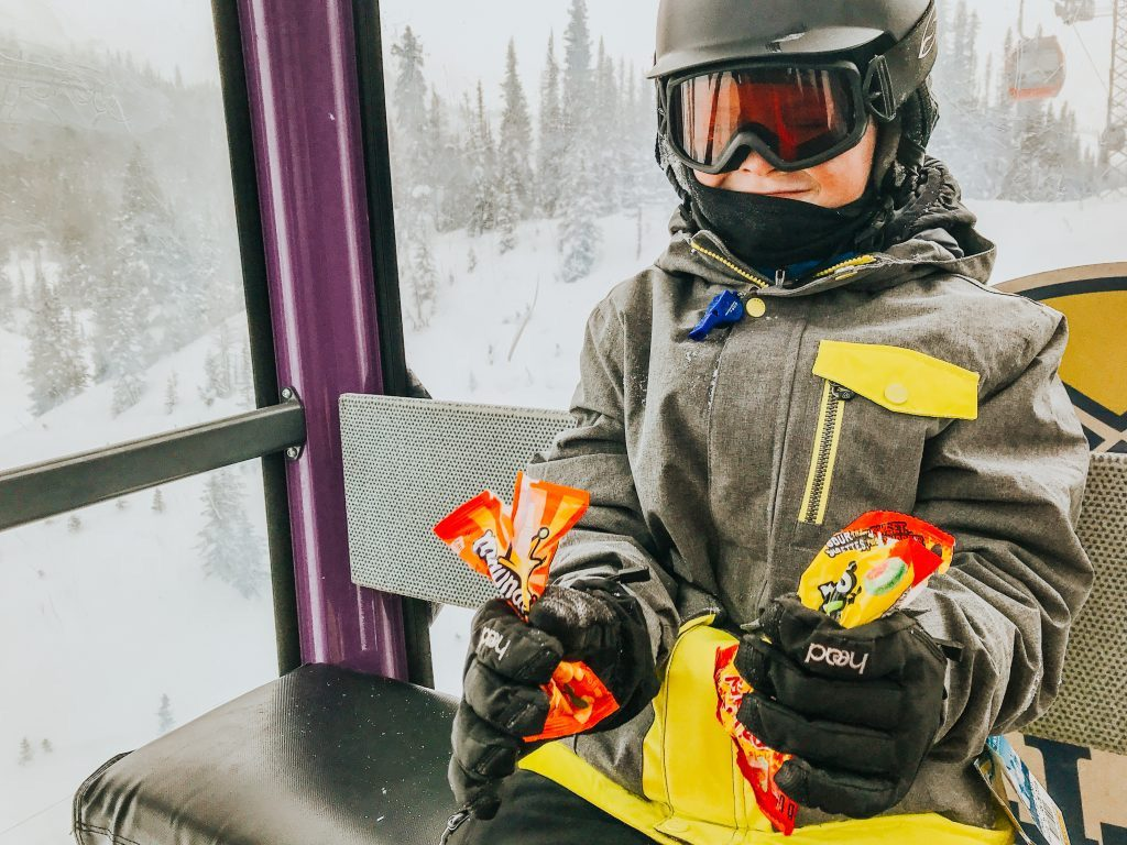 Boy with snacks on gondola at Sunshine Village Ski & Snowboard Resort Banff