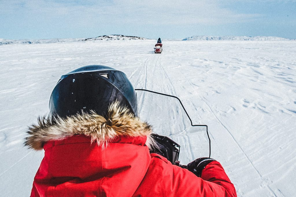 woman-on-sled-snowmobiling-through-the-arctic