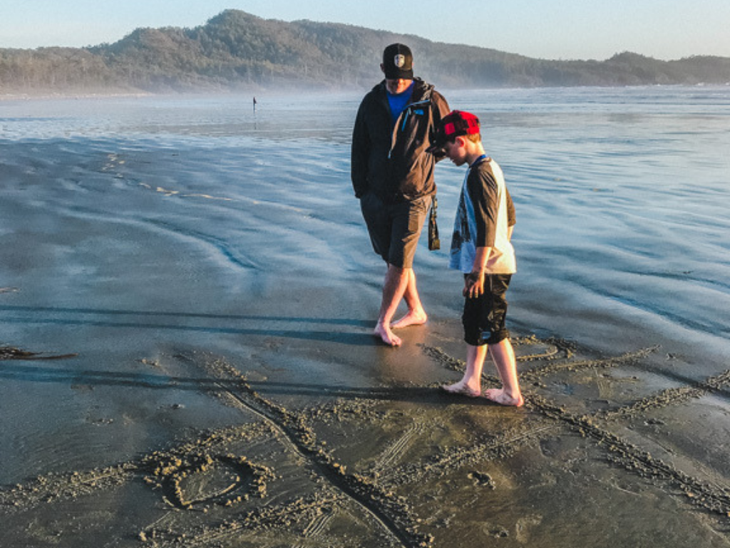 father-and-son-playing-on-beach-in-front-of-long-beach-lodge-in-tofino